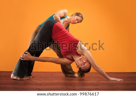 Yogasana instructor with student stretching over orange background - stock photo