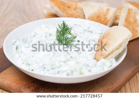 yoghurt sauce tzatziki with herbs, cucumber and garlic, close-up, horizontal - stock photo