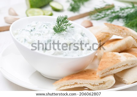 yoghurt sauce tzatziki with pieces of pita bread, close-up, horizontal - stock photo