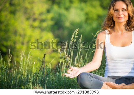 Yogi girl meditating isolated on beautiful nature. Woman in white singlet smiling with her fingers in yogic. - stock photo