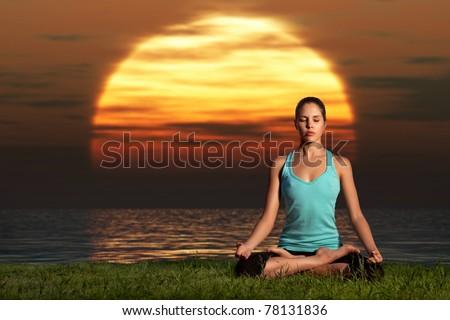 Yogi sunrise. A sportive beautiful woman training yoga on the beach at dawn. - stock photo