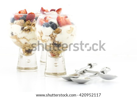 Yogurt Granola and Fruit Parfaits on a white background - stock photo