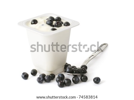 Yogurt in a plastic box with blueberries and spoon - stock photo