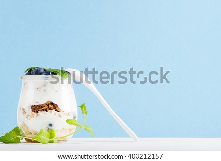 Yogurt oat granola with jam, blueberries and green leaves in glass jar on pastel blue backdrop, copy space - stock photo