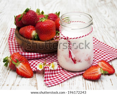 Yogurt served with fresh strawberries in a glass - stock photo