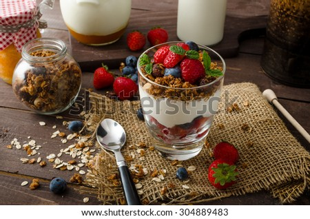 Yogurt with baked granola and berries in small glass, strawberries, blueberries. Granola baked with nuts and honey for little sweetness. Homemade yogurt - stock photo