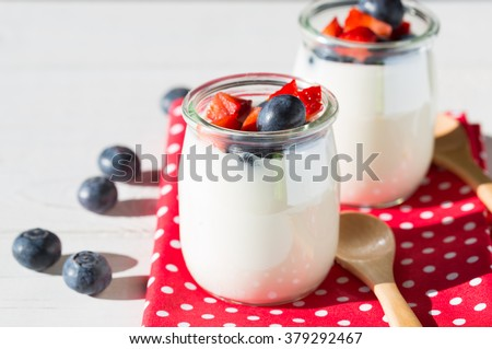 yogurt with berries and strawberries into pieces - stock photo