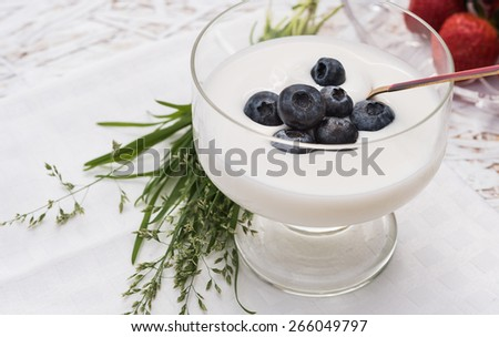 Yogurt with blackberry in glass cup on white wooden table with white towel, bouquet of grass, on background plate with strawberry - stock photo
