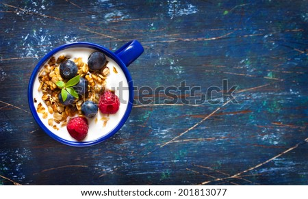 Yogurt with granola and fresh berries on an old wooden board with copy space for text. - stock photo