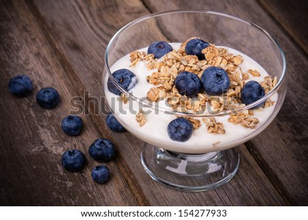Yogurt with granola and fresh blueberries, in glass bowl over old wood background. Vintage effect. - stock photo