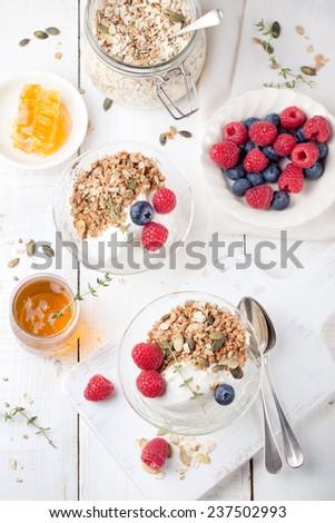 Yogurt with granola, honey and fresh berries in a ceramic bowl on white background. - stock photo