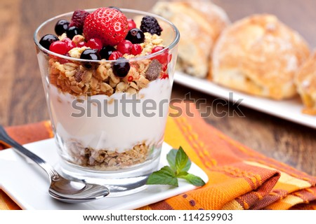 yogurt with muesli and berries in small glass - stock photo