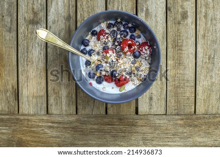 Yogurt with muesli and fresh blueberries, raspberries, sunflower seeds in bowl over old wooden background.   - stock photo