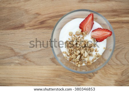 yogurt with muesli and strawberries, a delicious dessert with berries, healthy Breakfast on wooden background, macro - stock photo