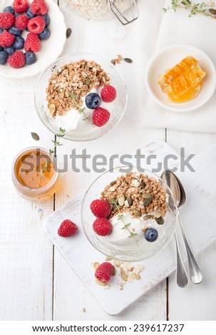 Yogurt with muesli , honey and fresh berries. Healthy breakfast. - stock photo
