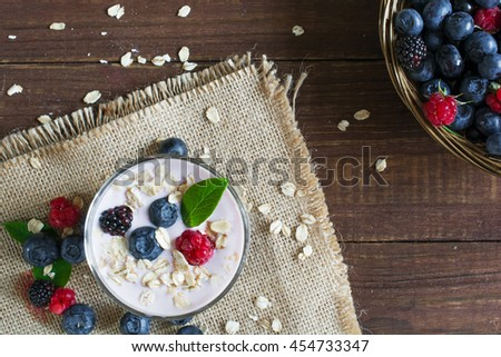 Yogurt with oatmeal or muesli and fresh berries in a glass and ripe berries in a wicker bowl. healthy breakfast. top view - stock photo