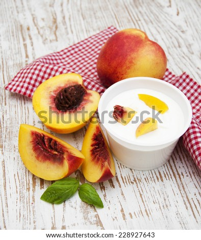 Yogurt with peaches on a wooden background - stock photo
