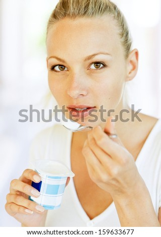 Yogurt woman eating yoghurt as breakfast - stock photo