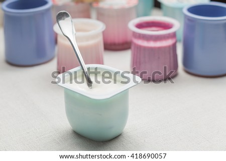 Yogurts assortment  in plastic bowls on white textile background. Natural and fruit healthy, diet, gourmet dessert for granola breakfast. Sweet yogurts closeup. - stock photo