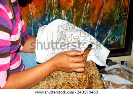 YOGYAKARTA, INDONESIA - SEPTEMBER, 13: Indonesian woman applying wax on batik in workshop. Batik is traditional art made by applying wax and dye on fabric. In Yogyakarta, Indonesia on Sept 13, 2014 - stock photo
