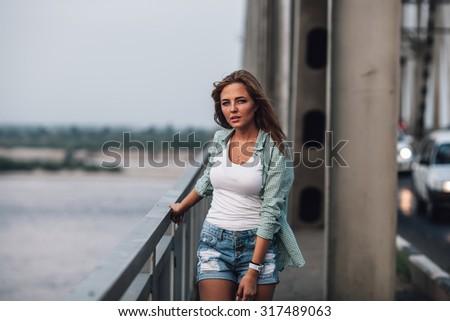 yong adult beautiful woman standing on bridge - stock photo