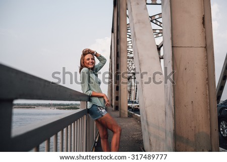 yong adult beautiful woman standing on bridge and smiling, holding her hairs with hands - stock photo