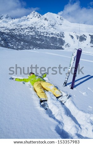 Yong woman laying in snow, enjoying rest, with her ski standing close with mountain on the background - stock photo