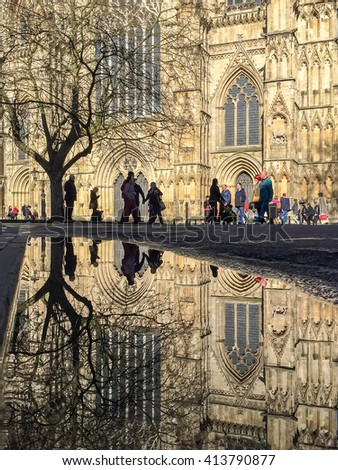 YORK, UK - April 30: The Great West Door of York Minster reflected in an 'April Shower' puddle on April 30, 2016 in York. - stock photo