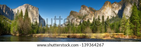 Yosemite Valley panorama showing the upper Yosemite Falls and the Bridalveil Falls with the Merced river in the foreground - stock photo