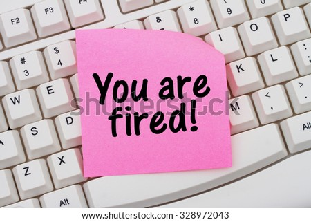 You are fired, Computer Keyboard with a pink blank sticky note with text You are fired - stock photo