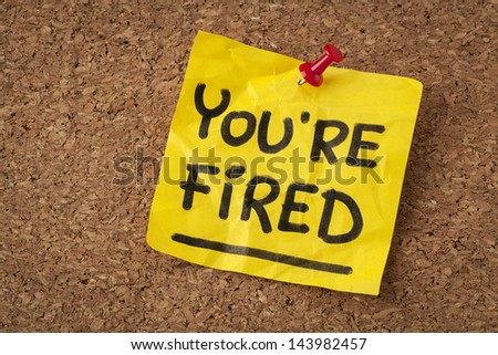 you are fired note - handwriting on orange sticky note - stock photo