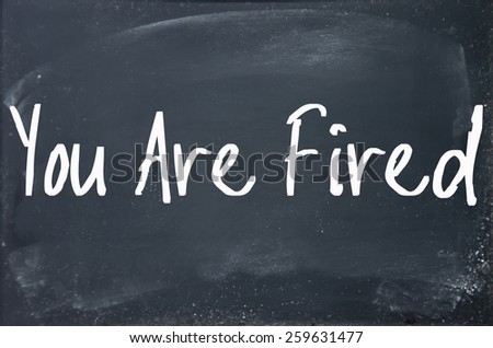 you are fired text write on blackboard - stock photo