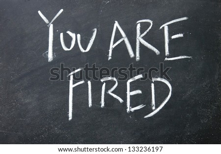 you are fired title written with chalk on blackboard - stock photo