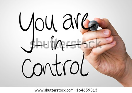 You are in Control hand writing with a black mark on a transparent board - stock photo