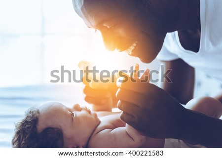 You are my everything! Side view of happy young African man playing with his little baby and smiling while lying in bed - stock photo