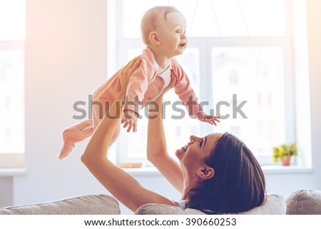You are my little bird! Side view of cheerful beautiful young woman holding baby girl in her hands and looking at her with love while sitting on the couch at home - stock photo