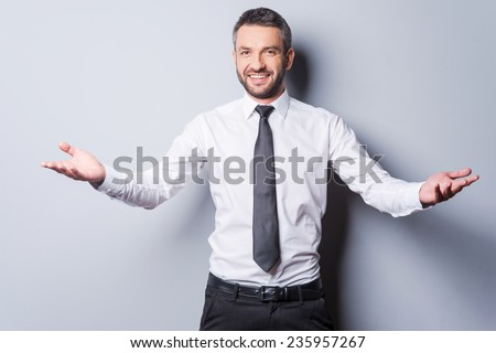 You are welcome! Cheerful mature man in shirt and tie gesturing welcome sign and smiling while standing against grey background - stock photo