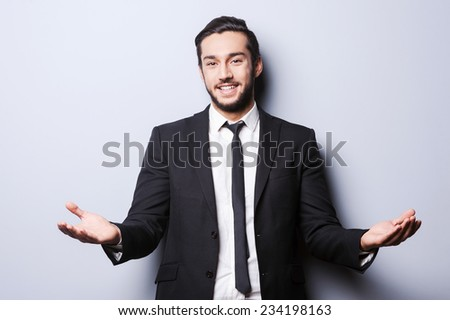 You are welcome! Cheerful young man in formalwear looking at camera and gesturing while standing against grey background - stock photo