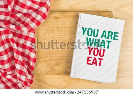 You Are What You Eat Message in Recipe Notebook on Kitchen Table, Concept of Guidelines for Proper Nutrition with Copy Space, Top View. - stock photo
