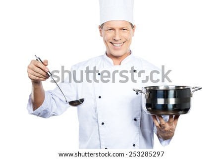 You should try this soup. Cheerful mature chef in white uniform holding casserole and scoop while standing against white background - stock photo