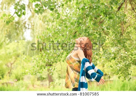 You woman throws her arms out enjoying the park - stock photo