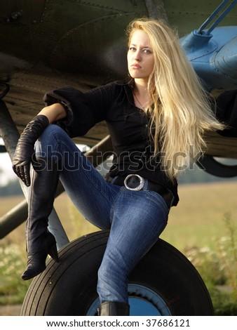 Youg blond woman sitting on vintage airplane landing gear - stock photo