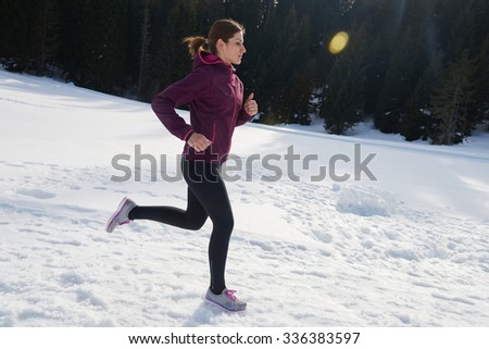 yougn woman jogging outdoor on snow in forest, healthy winter lifestyle and recreation - stock photo