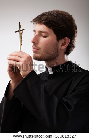 Youn christian priest is praying to cross - stock photo