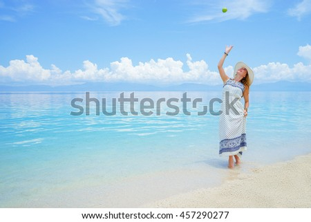 Youn europian woman in light dress and hat is walking on white sand beach near calm amazing sea playing with green apple at sunny day - stock photo