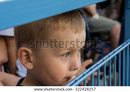 Youn white boy watchin football game at stadium - stock photo