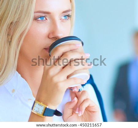 Yound woman drink coffee at office, standing - stock photo