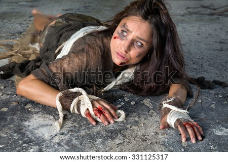 Young abused and frightened woman sitting on the floor of a derelict building - stock photo