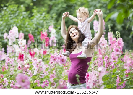 Young active and fit pregnant mother playing with her baby daughter in a blooming garden with pink flowers - stock photo