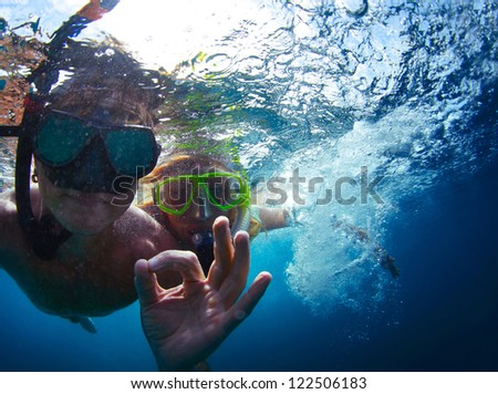 Young active couple snorkeling in a sea and giving ok signal - stock photo